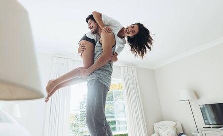 Foto de Young man standing on bed and carrying his girlfriend on his shoulder. Couple in playful mood in bedroom. - Imagen libre de derechos