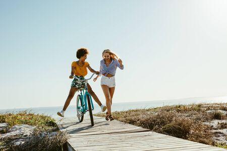 Foto de Two young women having fun with a bicycle at the beach. Woman running with friend riding a bike on boardwalk. - Imagen libre de derechos