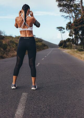Foto de Rear view of young woman standing on an empty road getting ready for a run. Sporty woman ready for her morning workout. - Imagen libre de derechos