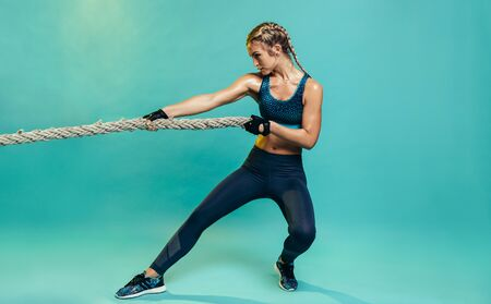 Photo pour Tough young woman exercising with battling rope in studio. Healthy sports woman working out with battle rope over blue background. - image libre de droit
