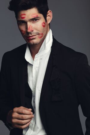 Photo pour Stylish young guy covered with kiss marks on face. Good looking model standing against grey background. - image libre de droit