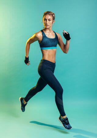 Foto de Fit and healthy woman running. Female runner sprinting on blue background. - Imagen libre de derechos