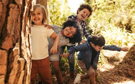 Foto de Cute smiling kids peeking out from behind the tree in the park. Group of children enjoying playing hide and seek in a forest. - Imagen libre de derechos