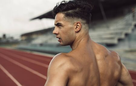 Photo pour Rear view of healthy young man standing on track field. Muscular man taking a break from workout at a stadium. - image libre de droit