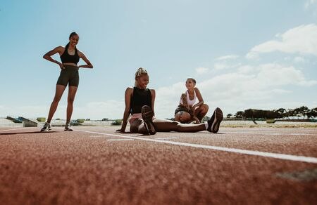 Photo for Female athletes taking a break after workout sitting on the running track in the stadium. Women relaxing and smiling after training. - Royalty Free Image