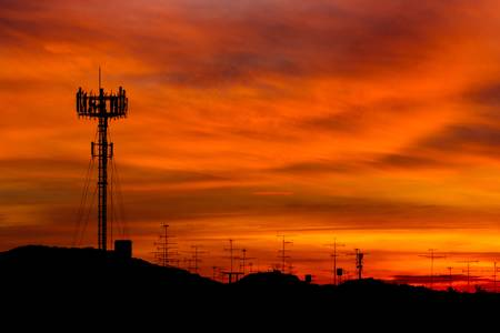 Telecommunications tower with sunset sky, silhouette