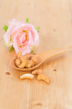 Cashew nuts in wooden spoon.