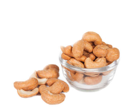 Glass bowl full with cashew nuts. Isolated on a white background.