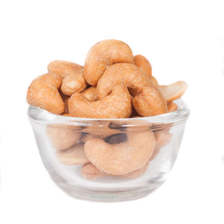 Glass bowl full with cashew nuts. Isolated on a 