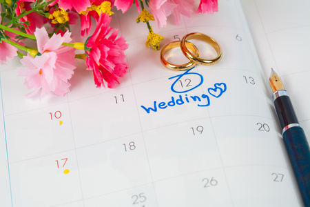 Photo pour Wedding note on a calendar sets a reminder for the wedding day with flower and pen - image libre de droit