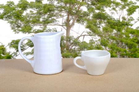 Photo pour White coffee cup and jar on wood table with nature background. - image libre de droit