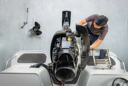 Photo for Repairing engines on aluminum boats , The technician is removing the boat parts to make the paint - Royalty Free Image
