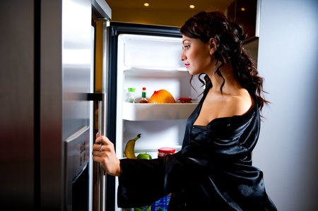 Young woman looking for something to eat inside the fridge