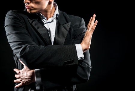 Man in elegant black jacket and blue shirt posing over black background