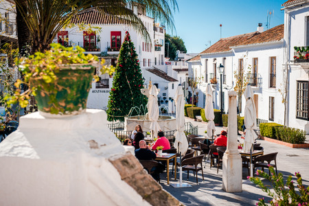 Mijas, Spain- January 5, 2014: Tourists sitting in a sidewalk cafe on central street of Mijas. Mijas is a lovely Andalusian white village on the Costa del Sol. Spain