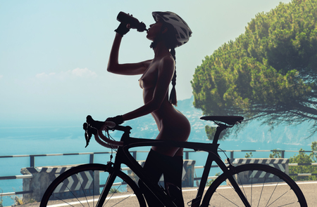 Naked woman with a bicycle drinking a water. Summer landscape, roadside