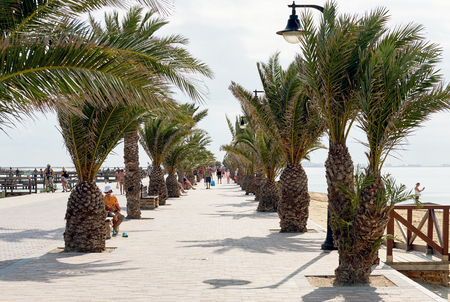 San Pedro del Pinatar, Spain - November 23, 2017: Palm-lied promenade of San Pedro del Pinatar, touristic heart of the Costa Calida. This small seaside town is famous for its therapeutic mud baths and salt flats.