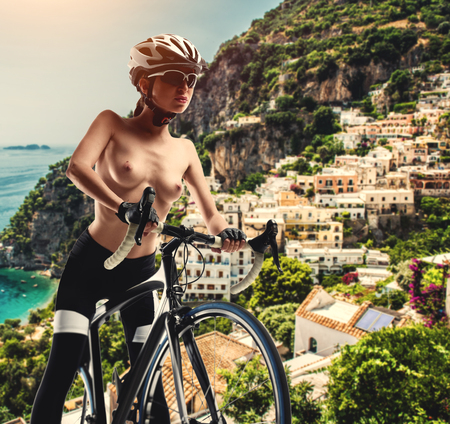 Naked woman with a bicycle against Amalfi coast. Italy