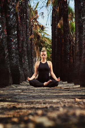 Young woman in black sportswear sitting in lotus position and meditating outdoors. Woman in early gestation. Pre natal exercising, healthy lifestyle. Attractive blond woman in tropical nature, path lined with black trunks of palm trees, unusual scenery. Looking at camera