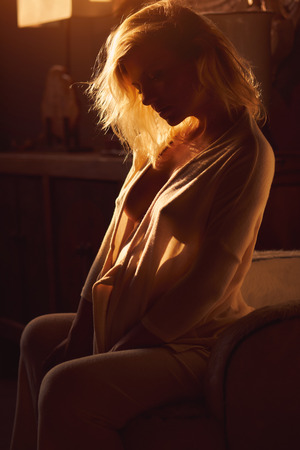 Sensual beautiful thoughtful pensive pregnant woman sitting in bedroom at home. Relaxed blond fashionable young female in morning gown or bathrobe sitting with naked breast. Shadows, romantic mood