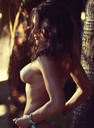Foto de Side view naked 30s woman bare breast posing on tropical trees palm tree trunks background, sunlight illuminates her body - Imagen libre de derechos