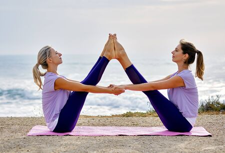 Photo pour Two yogi women in activewear do yoga exercise sit on coast make wide legged buddy boat pose near sea, increase body flexibility inner balance, reduce anxiety stress healthy lifestyle side view concept - image libre de droit
