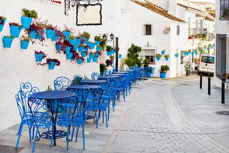 Photo pour Mijas Pueblo Blanco, charming small village, picturesque empty street in old town with bright blue tables chairs of local cafe, flower pots hanging on white washed houses walls, Costa del Sol, Spain - image libre de droit