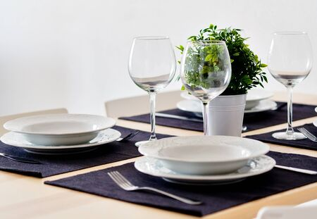 Photo pour Close up new white porcelain tableware plates on purple place mats and empty wine glasses ready for dinner. Table settings wait for guests at home or restaurant, artificial potted plant for decoration - image libre de droit