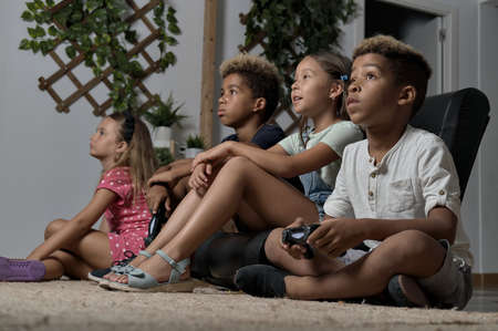 Photo for Four pretty multi national kids play to play station seated together at home. Alpha generation offspring addicted with virtual games problem concept - Royalty Free Image