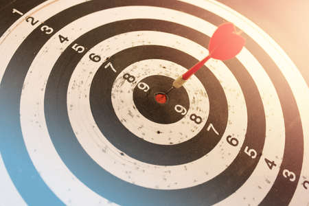 Photo pour Dart in bulls eye of dartboard with shallow depth of field concept for hitting target - image libre de droit