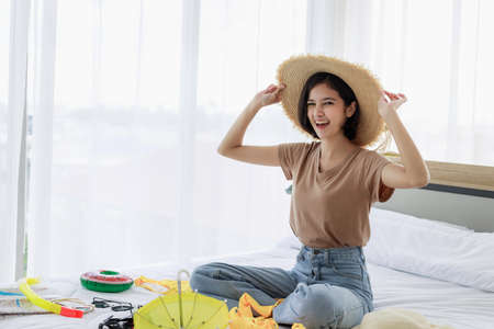 Photo pour Young Asian woman smiling and experimenting with hats and packing suitcases for summer vacation travel in his bedroom. concept of travel in summer and holiday. - image libre de droit