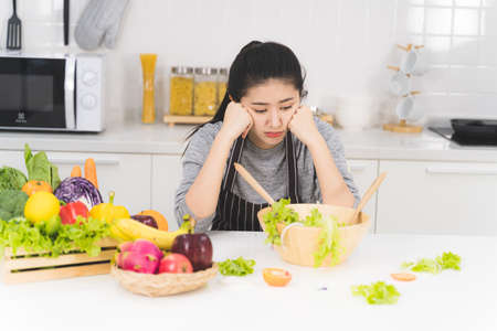 Photo pour Young woman or housewife is bored of cooking, which consists of a variety of fruits and vegetables for the family. - image libre de droit