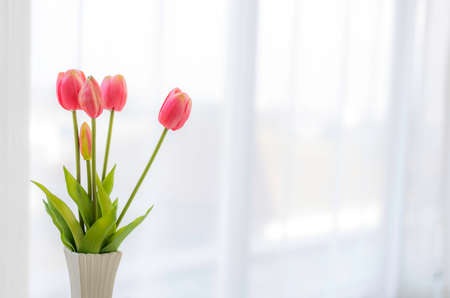 Photo pour beautiful fake pink tulips in white vase in bed room with soft sun light and white curtains copy space. - image libre de droit