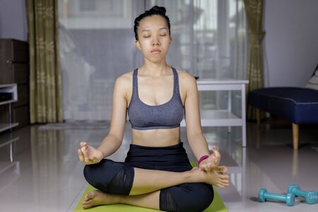 Photo pour International Day of Yoga concept Asian woman doing meditation for yoga athlete sitting on an exercise mat at home. - image libre de droit