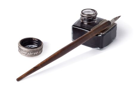 An antique glass inkwell and wooden pen isolated over white background
