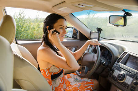 Pretty woman driver sitting behind the steering wheel talking on her mobile phone with the car safely parked at the roadside