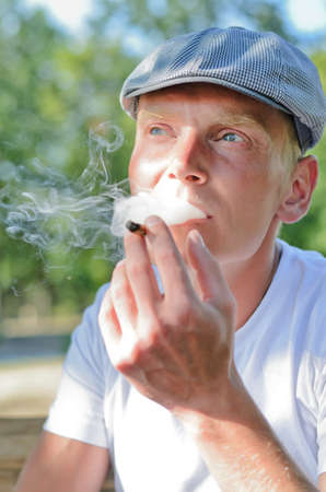 Man puffing on a home made cigarette that he has rolled from a loose tobacco blend relaxing outdoors in a park enjoying the fresh air