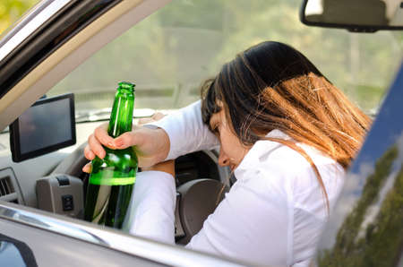 Drunk woman driver passed out in the car with her head resting on her arm on the steering wheel and her bottle of booze clasped in her hand