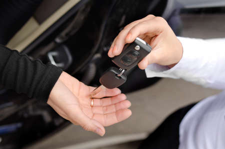 Close up view of the hands of a woman handing over a set of car keys to a second woman holding out her hand, conceptual image