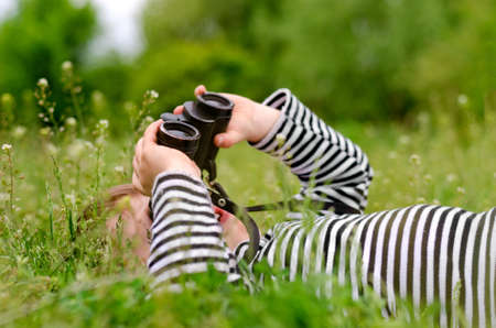 Photo pour Young child using a pair of binoculars to look up into the sky as he lies on back in a grassy rural meadow enjoying a day in nature - image libre de droit