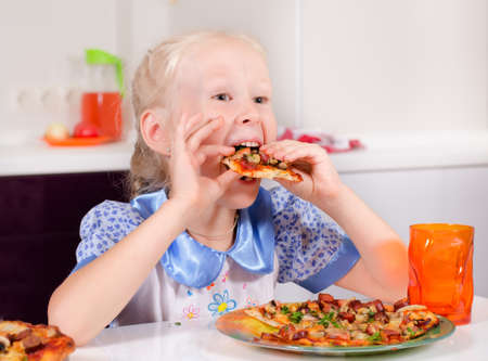 Happy young girl eating delicious homemade pizza in the kitchen