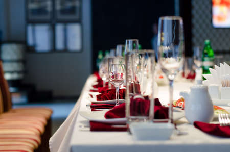 Formal stylish setting on a dinner table with elegant glassware and red linen for a party or celebration of a special event