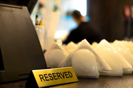 reserved sign and crockery with folded paper serviettes on a bar counter ready to be used at table for customers