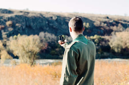Full Length Shot of a Boy Scout in Uniform Holding a Compass to Find Direction at the Field.