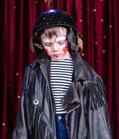 Head and Shoulders Close Up of Young Boy Wearing Clown Make Up, Leather Jacket and Helmet Staring Solemnly Downward on Stage