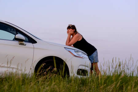 Calm Brunette Woman Leaning on Hood of White Family Car Parked in Green Field with Long Grass and Enjoying View of Sunset While Leaning on Elbows