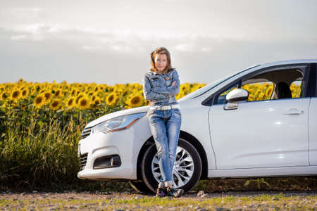 Young woman enjoying a day in the country standing leaning against her car in front of a field of colorful yellow sunflowers