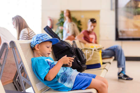 Little boy sitting in an airport departure hall contentedly playing on his tablet or mobile phone as he waits for his flight with his luggage