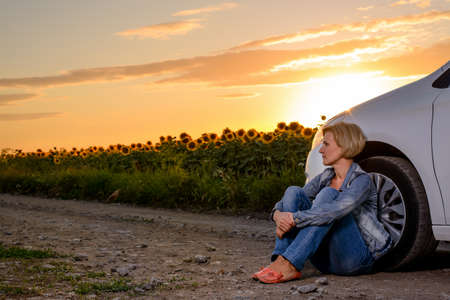 Full Length of Blond Woman Sitting on Ground Leaning Against Car on Dirt Road Surrounded by Sunflower Fields at Sunset with Warm Sunlight - Woman with Car Trouble