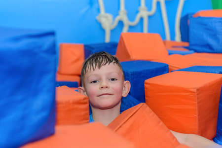 Cute happy little boy crouched down amongst loose colorful red and blue plastic cubes at a funfair or playground grinning at the camera